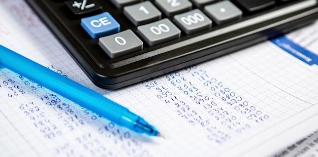 Długopis i kalkulator. ściana przedmioty do prowadzenia działalności w biurze w kompozycji.