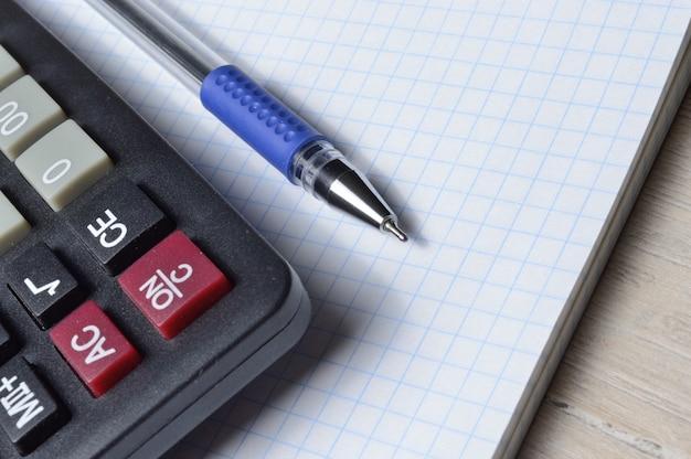 Długopis i mikrokalkulator leżą na zeszycie w kratkę