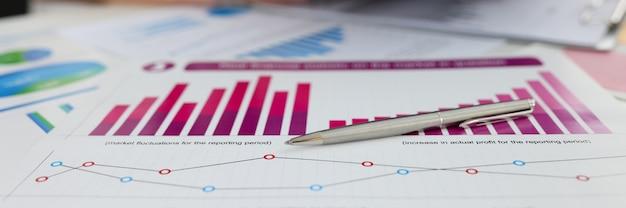 Długopis leżący na dokumentach z wykresami i diagramami zbliżenie wzrost zysku w biznesie