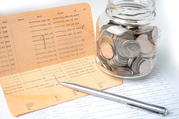 Długopis na koncie banku książki z monetami w szklanym słoju.