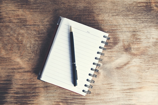 Długopis na notatniku na drewnianym stole