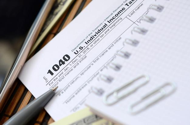 Długopis, notatnik, smartfon i rachunki za dolary leżą na formularzu podatkowym 1040 us