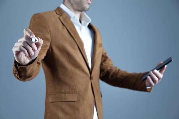 Długopis ręką człowieka w ekranie na szarym tle