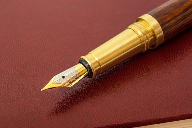 Długopis z pozłacanym długopisem na brązowym notatniku do notatek z bliska