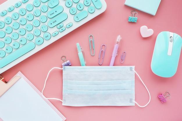 Długopisy biurowe i spinacze do papieru wystają z maski medycznej. nowoczesne miejsce pracy w koronawirusie pandemicznym.