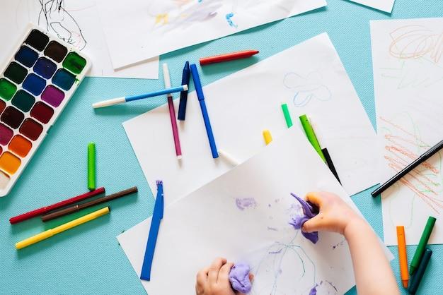 Długopisy dziecięce, kolorowe kredki i markery oraz farby - widok z góry