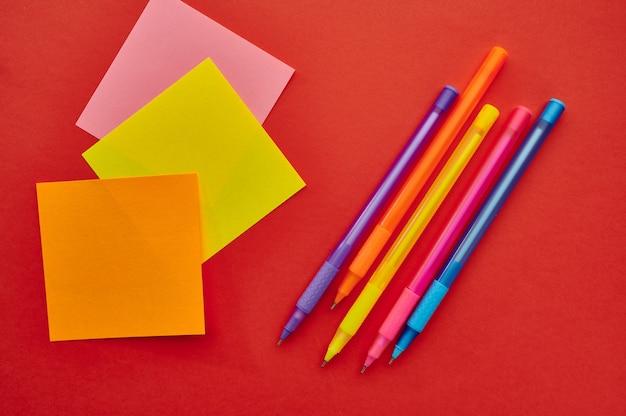 Długopisy i notesy zbliżenie, czerwone tło. artykuły biurowe, akcesoria szkolne lub edukacyjne, narzędzia do pisania i rysowania