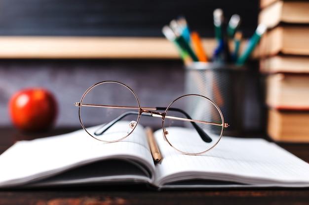 Długopisy, jabłko, ołówki, książki i szklanki na stole, na tle tablicy