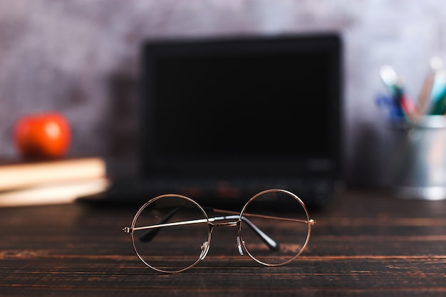 Długopisy, jabłko, ołówki, książki, laptop i okulary na stole, na tle tablicy