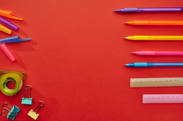 Długopisy, linijki i spinacze, czerwone tło. artykuły biurowe, akcesoria szkolne lub edukacyjne, narzędzia do pisania i rysowania