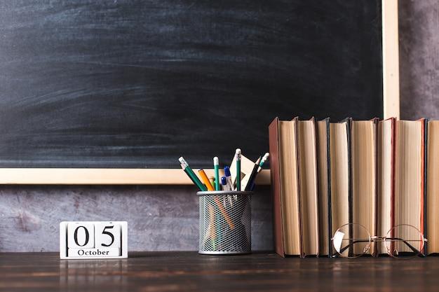 Długopisy, ołówki, książki i okulary na stole, na tle tablicy. kalendarz 5 października, miejsce na kopię.