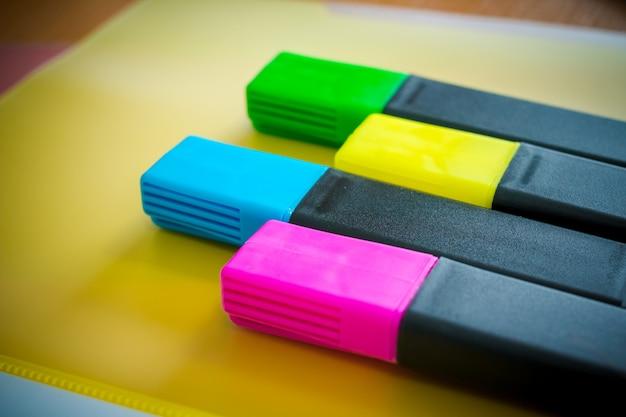 Długopisy, ołówki, nożyczki, linijka, spinacze, notatnik i marker na stole.