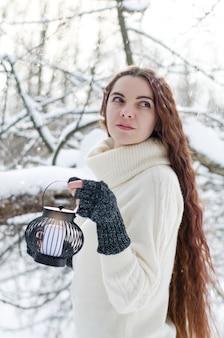 Długowłosa brunetka dziewczyna spaceru w lesie zimą z latarnią