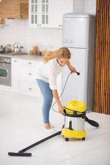 Długowłosa dorosła kobieta ma zamiar odkurzyć podłogę domu, rozwijając przewód z odkurzacza