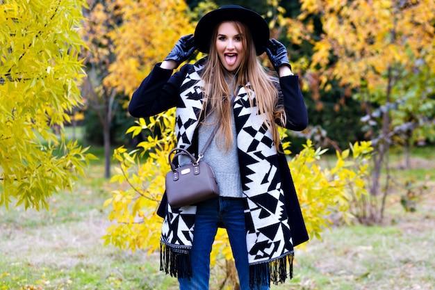 Długowłosa dziewczyna nosi dżinsy i bawi się szalikiem w jesiennym parku. atrakcyjna młoda kobieta w stylowym czarnym kapeluszu, spędzanie czasu w lesie i śmiejąc się.