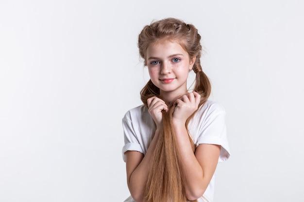Długowłosa dziewczyna. śliczna mała dziewczynka z dużymi niebieskimi oczami i jasnymi piegami, trzymająca obiema rękami swoje jedwabiste, jasne włosy