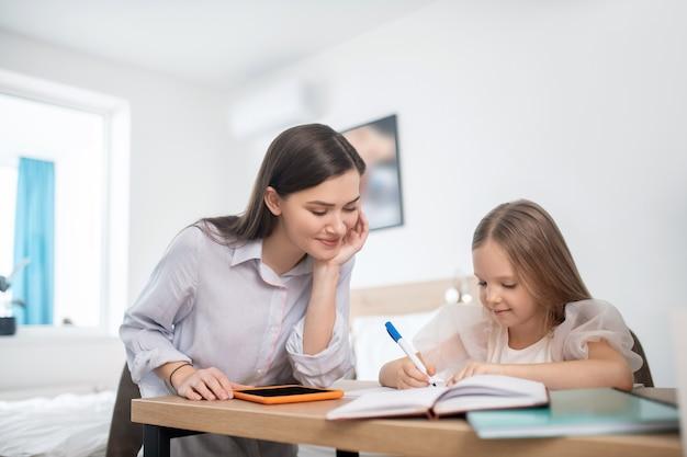 Długowłosa dziewczyna ucząca się w domu i wyglądająca na zaangażowaną