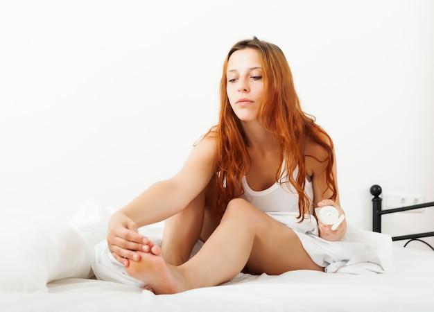 Długowłosa kobieta kładąc krem na nogach