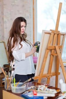 Długowłosa kobieta maluje farbami olejnymi