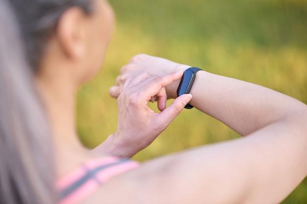 Długowłosa kobieta patrząca na zegarek na nadgarstku