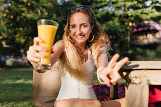 Długowłosa kobieta pije zimny sok w parku. urocza kaukaski kobieta zabawy na łonie natury z kieliszkiem pomarańczowego koktajlu.