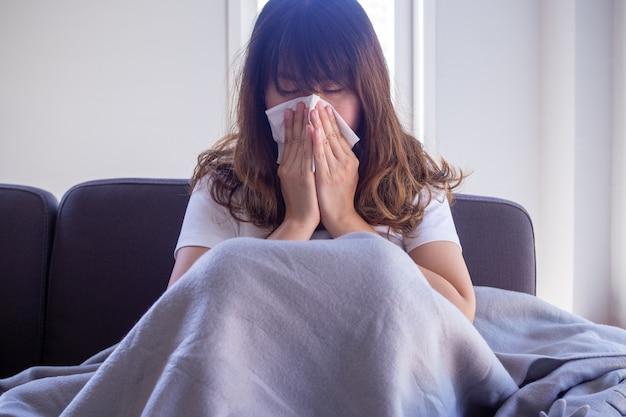 Długowłosa kobieta siedząca na kanapie cierpi na grypę, kaszel i kichanie. siedzi w kocu z powodu wysokiej gorączki i zakrywa nos chusteczką, ponieważ cały czas kicha.