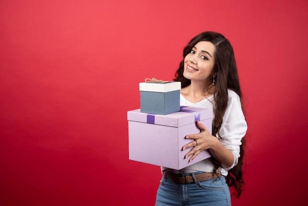 Długowłosa kobieta stojąca z obecnych pudełek na czerwonym tle. zdjęcie wysokiej jakości