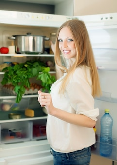 Długowłosa kobieta szuka czegoś w lodówce