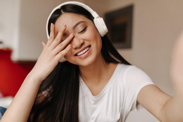 Długowłosa kobieta w białej bluzce zakrywa twarz ręką, śmieje się i robi selfie