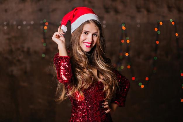 Długowłosa kobieta w błyszczącej sukience i czapce świętego mikołaja wyrażająca szczęście