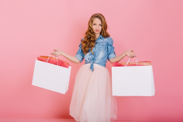 Długowłosa kręcona dziewczyna o niezadowolonym wyrazie twarzy pozuje z torbami z ulubionego sklepu odzieżowego. fascynująca młoda kobieta z elegancką fryzurą pozowanie po zakupach na białym tle na różowym tle