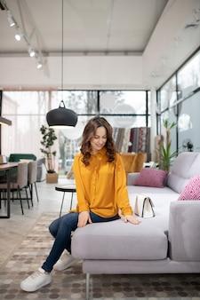 Długowłosa ładna kobieta siedzi na wygodnej kanapie