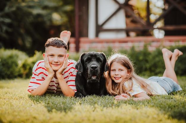 Długowłosa młoda dziewczyna i hipster teen boy w pozbawionych letnich koszulach zabijania na zielonej trawie z czarnym labrador retriever.