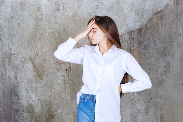 Długowłosa piękna dziewczyna w białej bluzce ma ból głowy