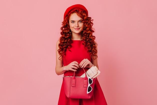 Długowłosa śliczna pani w czerwonym kapeluszu i jasnej sukience pozuje na różowej przestrzeni. kobieta o niebieskich oczach trzyma skórzaną torbę, magazyn i okulary.
