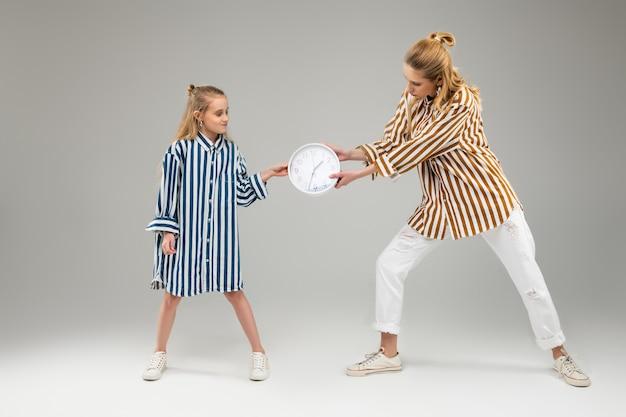 Długowłose ładne siostry żartobliwie walczą o okrągły zegar, ciągnąc go za sobą