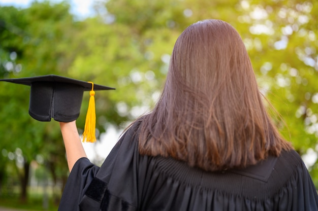 Długowłose studentki w czarnych sukienkach z falbanami wyrażające radość z ukończenia studiów.