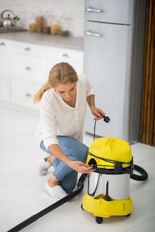 Długowłosy dorosły kobieta w ubranie przygotowuje odkurzacz do czyszczenia