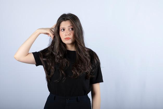 Długowłosy dziewczyna stoi i myśli na białej ścianie.