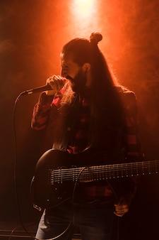 Długowłosy facet na gitarze śpiewa