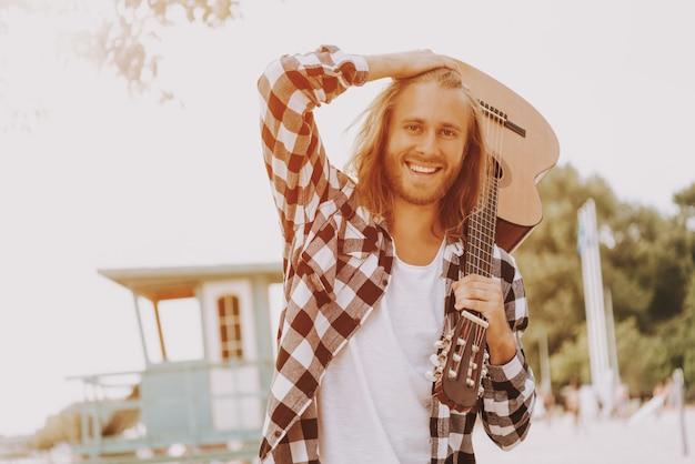 Długowłosy gitarzysta hipster muzyk na plaży.