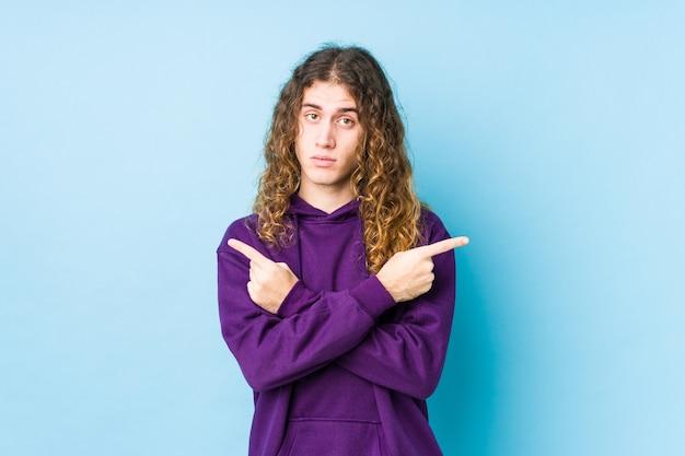 Długowłosy mężczyzna, pozujący odosobnione punkty bokiem, próbuje wybrać jedną z dwóch opcji.