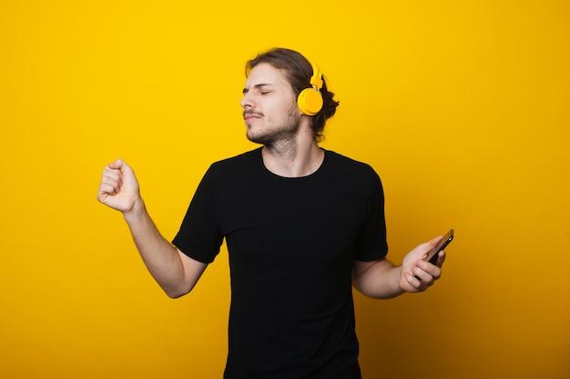 Długowłosy mężczyzna z brodą tańczy w słuchawkach i trzyma telefon komórkowy na żółtej ścianie studia, ubrany w czarną koszulkę