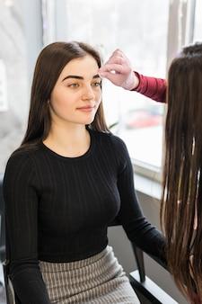 Długowłosy mistrz usuwa resztki czarnej farby dyskiem kosmetycznym