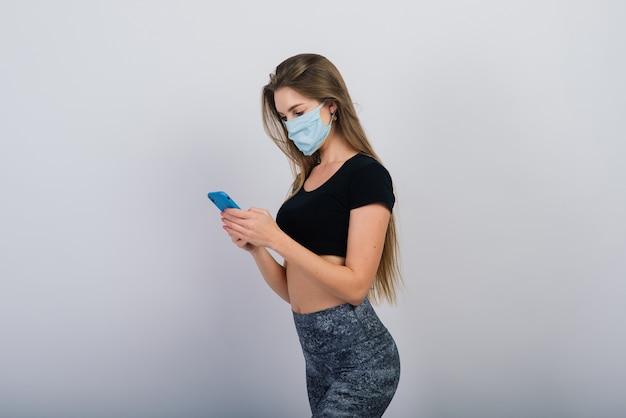 Długowłosy piękna dziewczyna z maską chirurgiczną, patrząc na smartfona i robi ćwiczenia fizyczne