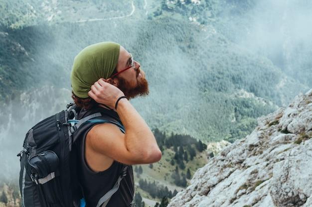 Długowłosy rudowłosy chłopak patrząc na góry