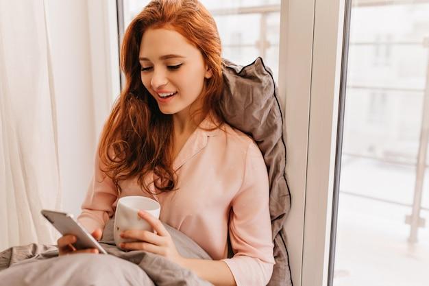 Długowłosy rudy kobieta czytająca wiadomość telefoniczną rano. ładny kaukaski dziewczyna siedzi na łóżku z filiżanką kawy i smartfonem.