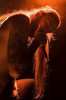 Długowłosy wokalista śpiewający na scenie