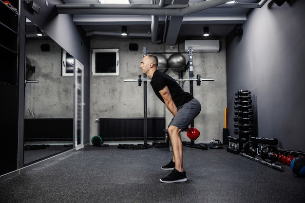 Dman w sportowym ubraniu, w czarnym t-shircie, stoi z rozstawionymi nogami i podnosi czajniczek obiema rękami na siłowni