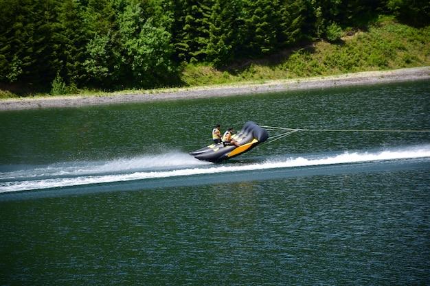 Dmuchana tratwa sportowa z dwoma mężczyznami szybko płynie po wodzie, prawie się od niej odrywając